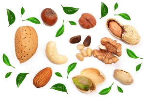 mixed of nuts decorated with leaves isolated on white background. Almond, cashew, peanut, hazelnut, pine nut, walnut