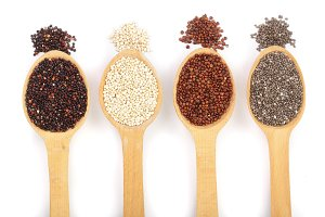 Black red white quinoa and chia seeds in wooden spoon isolated on white background. Top view