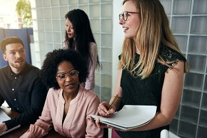 Smiling businesswoman talking with diverse coworkers in an office