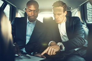 Businessmen discussing paperwork together in the backseat of a car