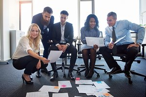 Smiling coworkers discussing paperwork together in a modern office