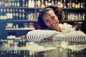 Smiling African entrepreneur leaning on the counter of her cafe