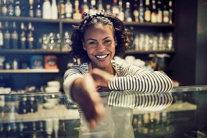 Friendly African entrepreneur shaking hands from behind her cafe counter