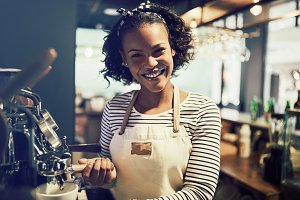 Smiling young African barista preparing fresh coffee in a cafe