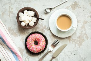 Donut with pink frosting and coffee