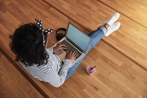 Young college student sitting on a campus floor working online