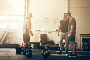 Fit men talking together while working out at a gym