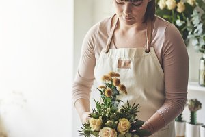 Young female florist making a flower bouquet in her workshop