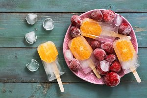 Popsicle. Refreshing fruit ice cream with orange slices served with frozen strawberries, ice cubes.