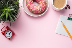 Flat lay Coffee Cup Donut Cactus Notepad Pencil Watch Player Vanilla on a Pink background