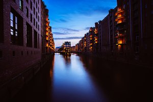 Blue hour in Warehouse District - Speicherstadt. Tourism landmark of Hamburg in twilight. View of Wandrahmsfleet in lantern light lamp. Place is located in Port of Hamburg within the HafenCity quarter
