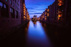 Wide perspective of Warehouse District - Speicherstadt in twilight. Tourism landmark of Hamburg. View of Wandrahmsfleet in light of lantern lamp. Port of Hamburg within the HafenCity quarter