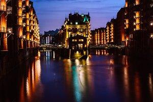 The Warehouse District - Speicherstadt in twilight. Tourism landmark of Hamburg. View of Wandrahmsfleet in light of lantern lamp. Port of Hamburg within the HafenCity quarter
