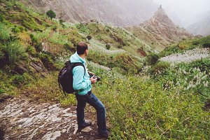 Santo Antao. Cape Verde. Photograph walking alone down the cobbled trekking trail towards green valley with huge rock.