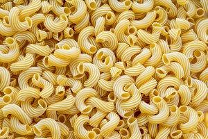 cavatappi macaroni lots of dry background.