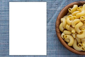 rigati macaroni in a wooden bowl on a blue knitted background. White space for text and ideas.