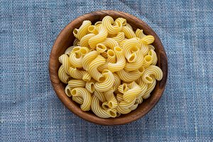 rigati pasta in a wooden bowl on a blue knitted background.