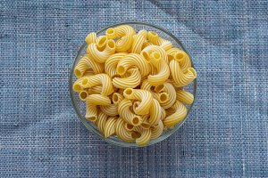 rigati Pasta in a glass bowl on a blue knitted background.