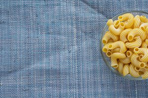 rigati Pasta in a glass bowl on a blue knitted background. With space for text.