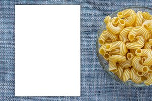 rigati Pasta in a glass bowl on a blue knitted background. White space for text and ideas.