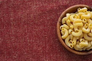 rigati pasta in a wooden bowl on a red brown cloth burlap background With space for text.