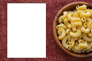 rigati pasta in a wooden bowl on a red brown cloth burlap background.White space for text and ideas.