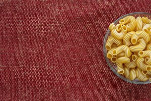 rigati pasta in a wooden bowl on a red brown cloth burlap background with a side. With space for text.