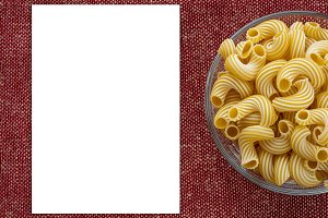 rigati pasta in a wooden bowl on a red brown cloth burlap background with a side. White space for text and ideas.