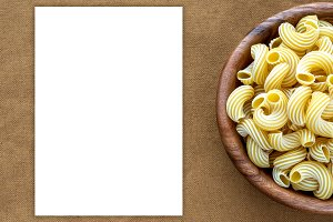 rigati pasta in wooden bowl on beige brown cloth burlap pattern with side. White space for text and ideas.