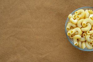 rigati pasta in glass bowl on beige brown cloth burlap background with side. With space for text.