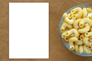 rigati pasta in glass bowl on beige brown cloth burlap background with side. White space for text and ideas.