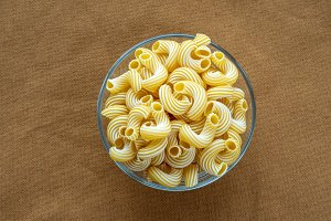 rigati pasta in a glass bowl on a beige brown cloth burlap background in the center.
