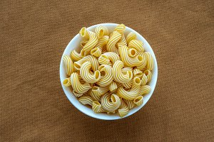 rigati pasta in a white bowl on a beige brown cloth burlap background in the center.