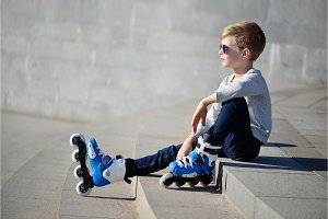 Boy siting with inline roller skates at outdoor skate park