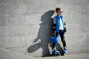 Young boy standing near grey wall with inline roller skates and all protection at outdoor skate park