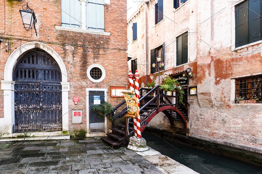 View Of Tiny Bridge With Flowers And Lampposts Into A Typical Venice Restaurant
