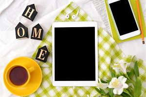 Flat lay tablet, phone, yellow cup of tea, laptop and flowers on white blanket with green napkin