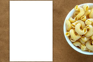 rigati pasta in white bowl on beige brown cloth burlap pattern with side. White space for text and ideas.