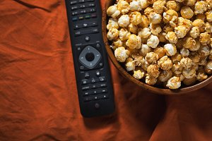 Wooden bowl with sweet popcorn and TV remote on orange bedding. Top view with copy space. Snacks and food for a movie