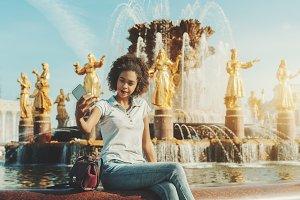 Girl taking selfie next to fountain