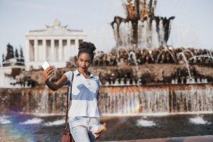 The girl taking selfie near fountain