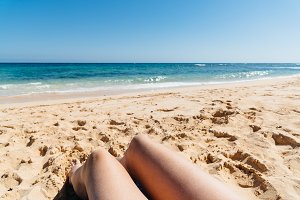 Mature woman legs sunbathing on the beach