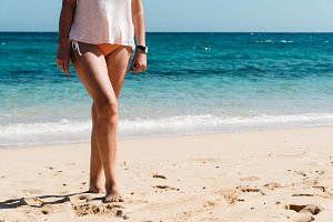 Woman legs closeup standing on white sand relaxing in beach wear