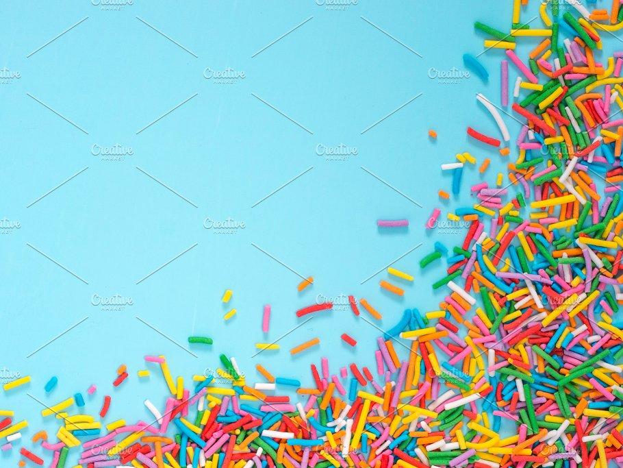 border frame of colorful sprinkles on blue background holiday