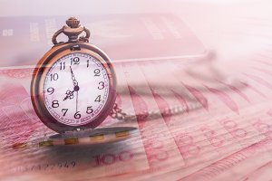 pocket watch over yuan banknotes