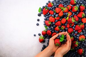 Hands holding fresh berries. Healthy clean eating, dieting, vegetarian food, detox concept. Close up of woman hands over berries background.