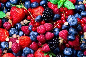 Assortment of strawberry, blueberry, raspberry, blackberry, currant, mint. Top view. Summer food. Macro of colorful berries background. Vegan, vegetarian and clean eating concept