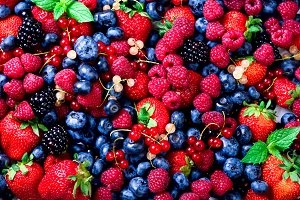 Macro colorful berries background. Top view. Summer food frame, border design. Assorted mix of strawberry, blueberry, raspberry, blackberry, currant, mint. Vitamin, vegan, vegetarian concept.