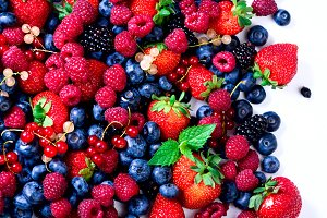 Assortment of strawberry, blueberry, currant, mint leaves. Food frame, border design. Vegan and vegetarian concept. Summer berries background with copy space for your text. Top view.
