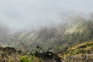 Panoramic shot of traveler making photo of amazing steep mountainous terrain with lush canyon valley on the path from Xo-Xo Valley. Camera on tripod.Santo Antao Island, Cape Verde